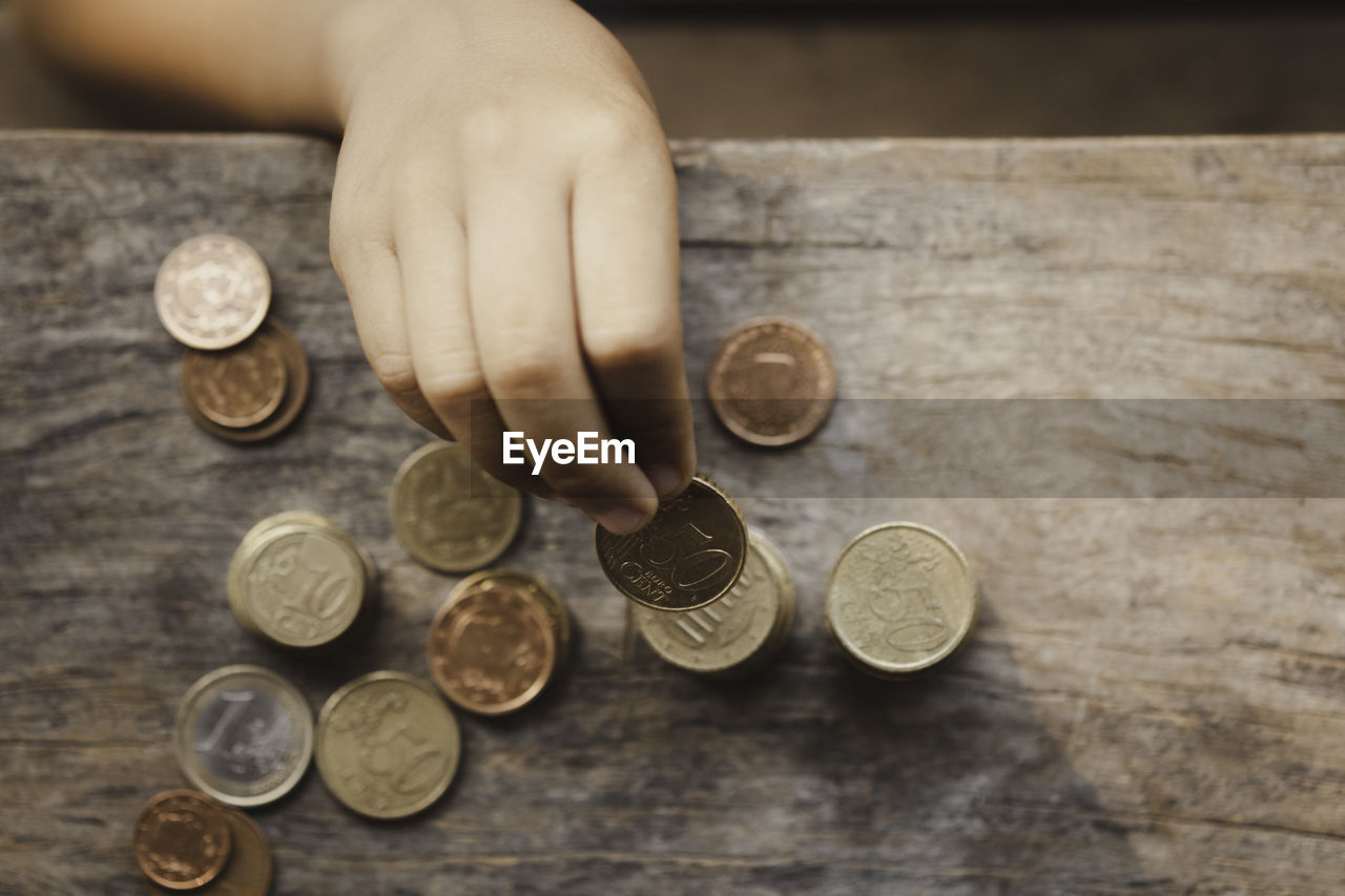 Close-up of hand holding coins on table