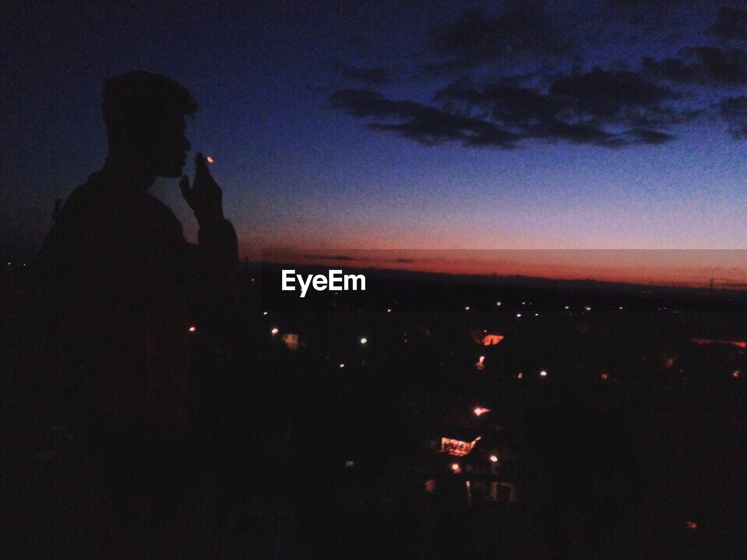 silhouette, night, real people, one person, sky, leisure activity, sunset, lifestyles, standing, photographing, bad habit, side view, outdoors, technology, nature, men, illuminated, beauty in nature, wireless technology, photography themes, scenics, women, young adult, people