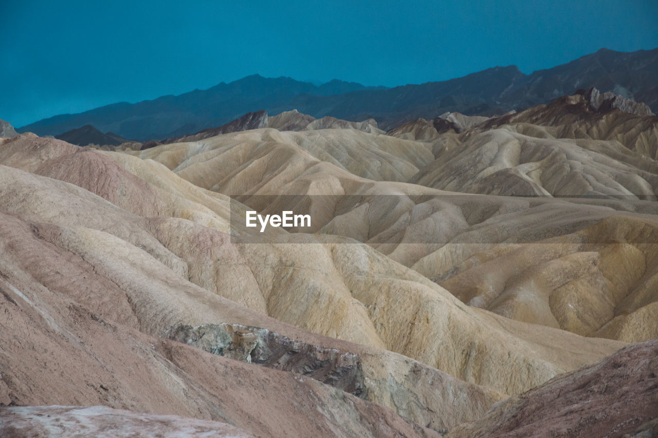 Scenic View Of Eroded Landscape Against Cloudy Sky At Death Valley National Park
