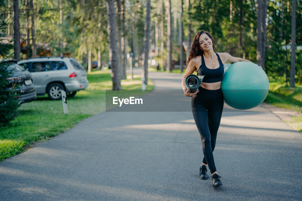 Portrait of woman with exercise mat and ball walking on road