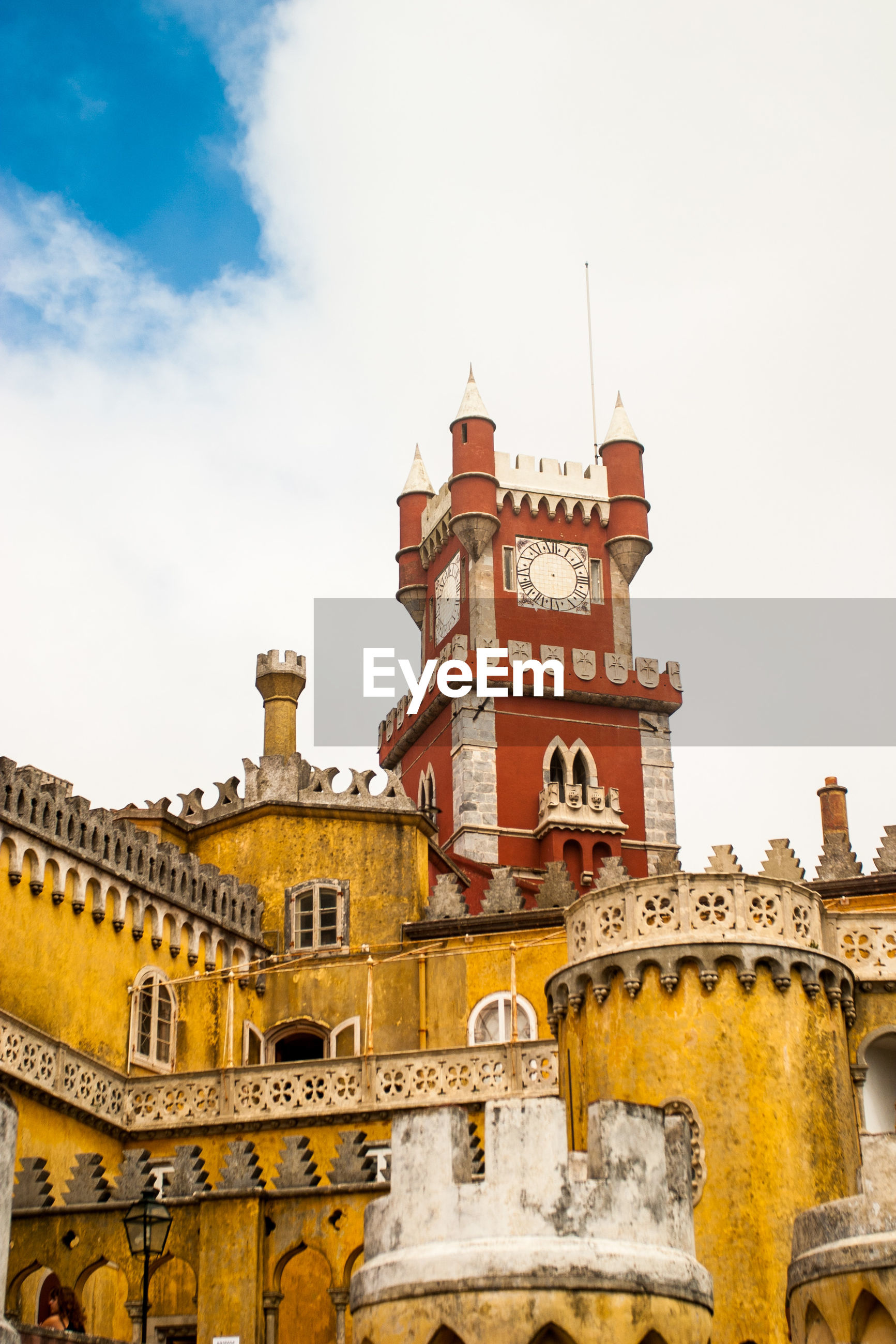 Low angle view of pena national palace against cloudy sky