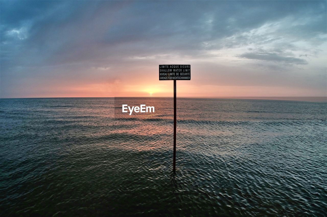 INFORMATION SIGN AGAINST SEA DURING SUNSET