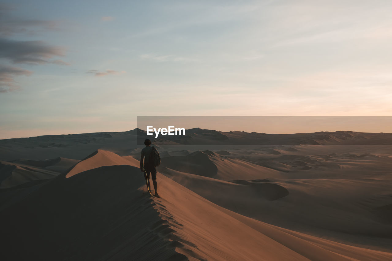 sky, scenics - nature, one person, beauty in nature, landscape, sand dune, desert, real people, non-urban scene, environment, tranquility, cloud - sky, land, tranquil scene, sunset, nature, leisure activity, rear view, lifestyles, climate, arid climate, outdoors, riding