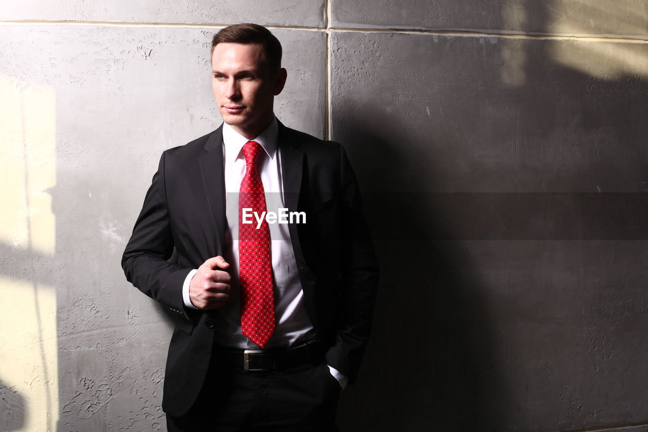 Mid adult businessman standing against wall