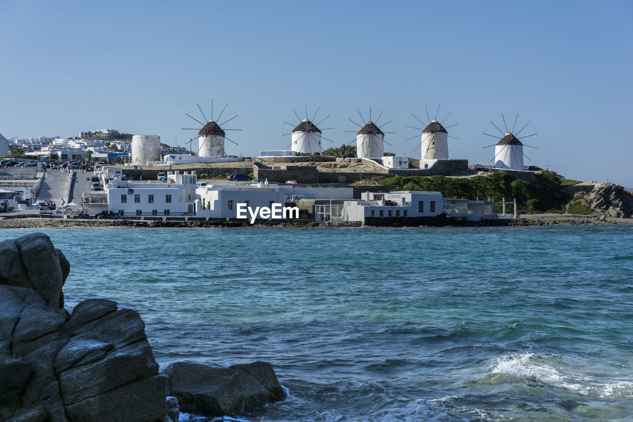 sea, water, built structure, clear sky, architecture, blue, day, outdoors, windmill, nature, wind power, building exterior, alternative energy, scenics, no people, beauty in nature, wind turbine, beach, sky