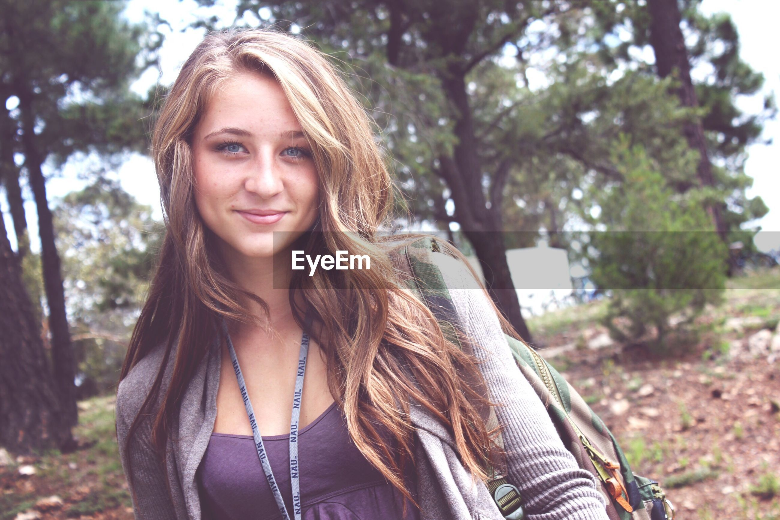 portrait, looking at camera, young adult, person, young women, front view, smiling, lifestyles, tree, leisure activity, long hair, casual clothing, focus on foreground, happiness, toothy smile, headshot, standing