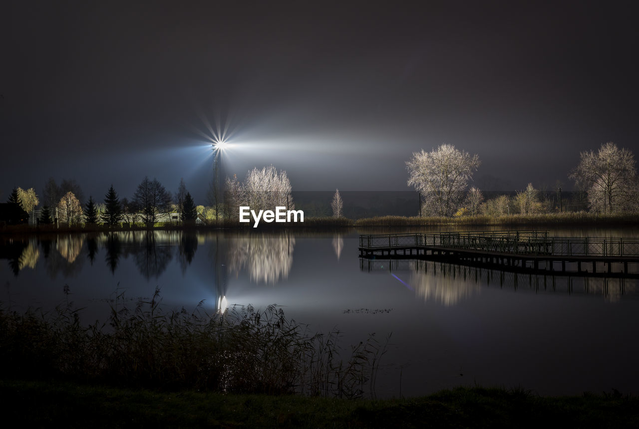 SCENIC VIEW OF LAKE AGAINST ILLUMINATED SKY AT NIGHT