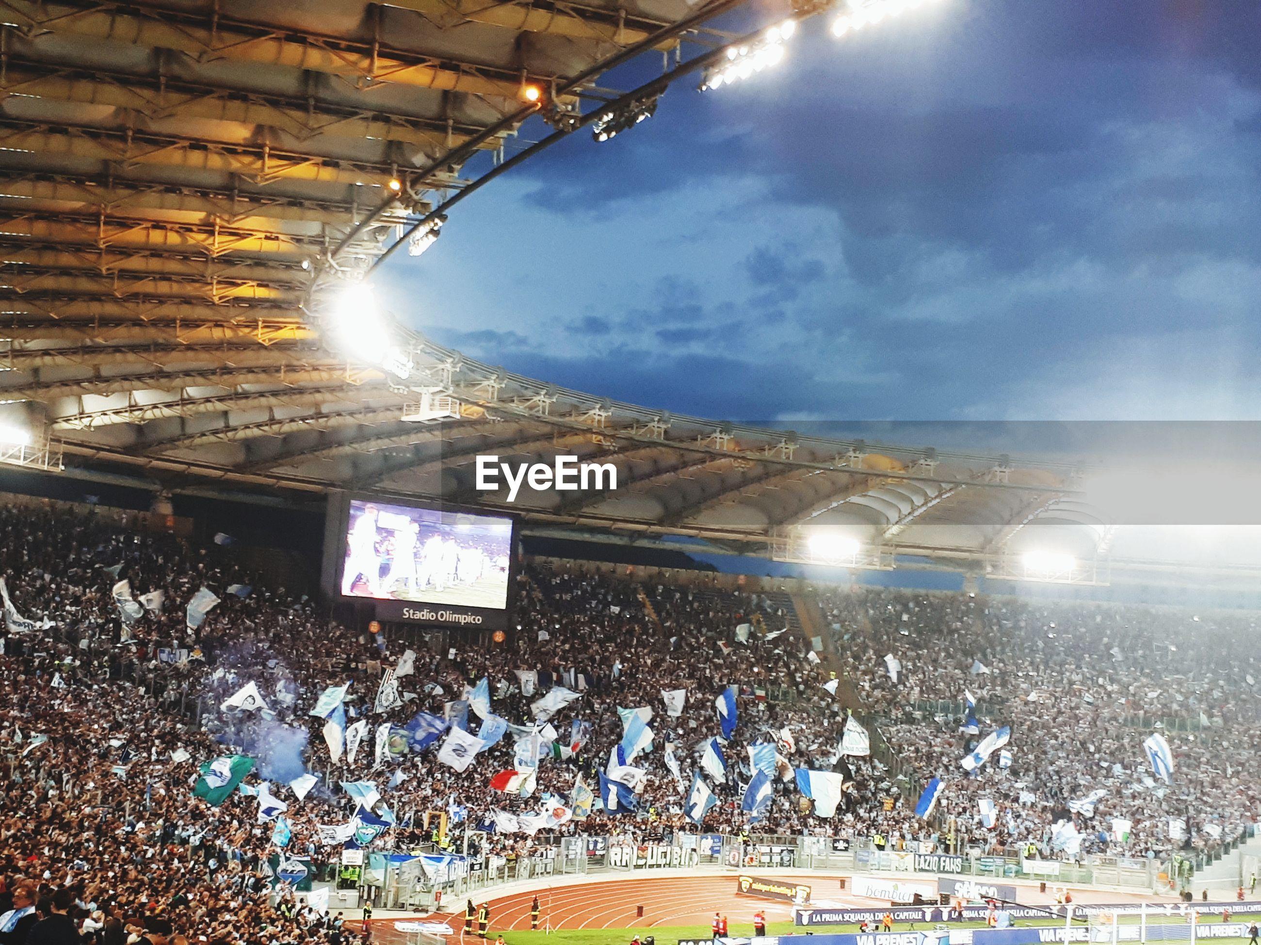 People at illuminated stadium against sky