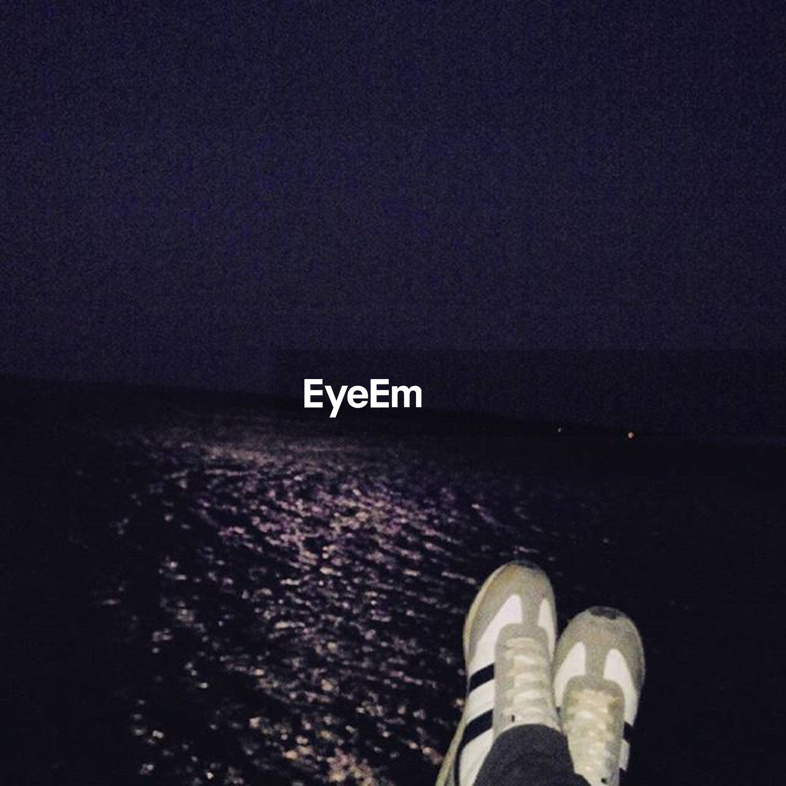 copy space, low section, water, night, shoe, person, clear sky, sky, tranquility, outdoors, tranquil scene, standing, nature, beach, scenics, personal perspective, blue, unrecognizable person