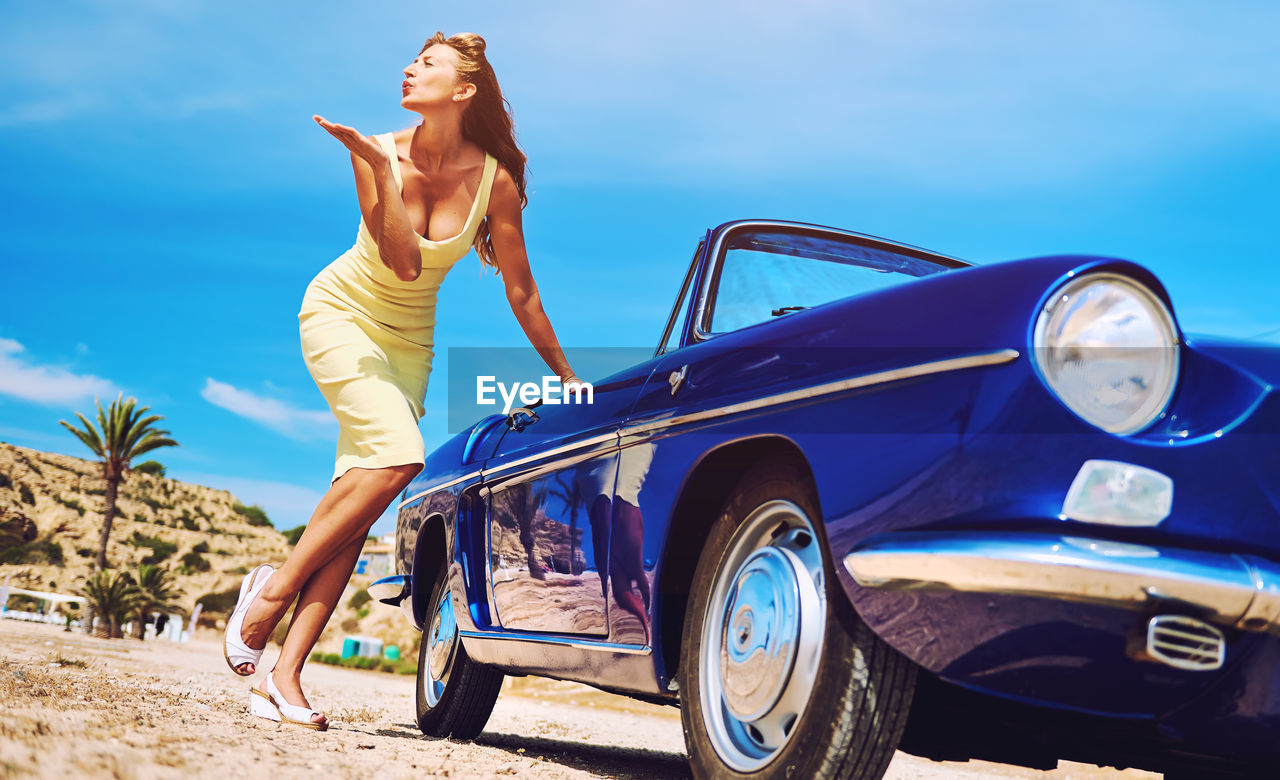 Woman Standing By Car Against Blue Sky