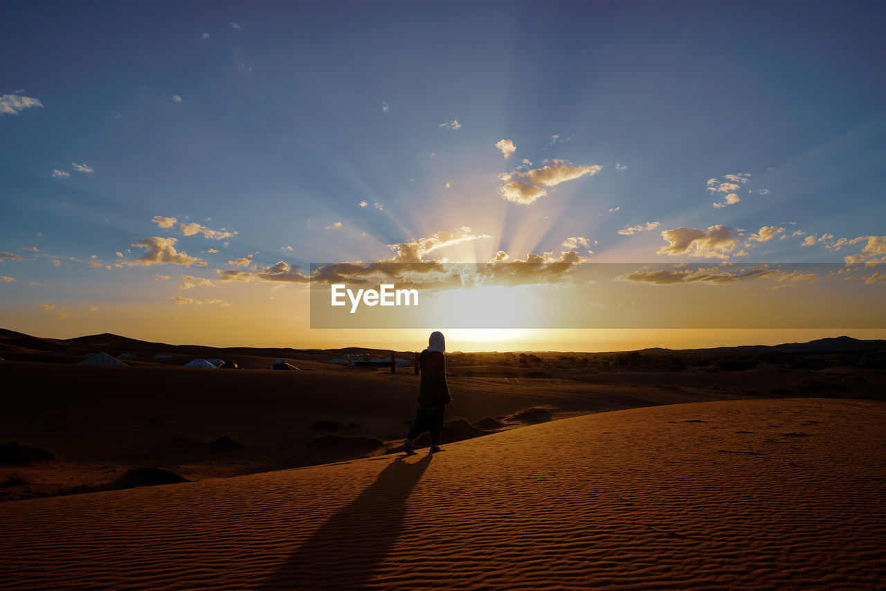 sky, sunset, beauty in nature, scenics - nature, land, one person, tranquility, lifestyles, tranquil scene, real people, silhouette, sunlight, leisure activity, cloud - sky, non-urban scene, standing, nature, orange color, sun, idyllic, outdoors, lens flare, arid climate