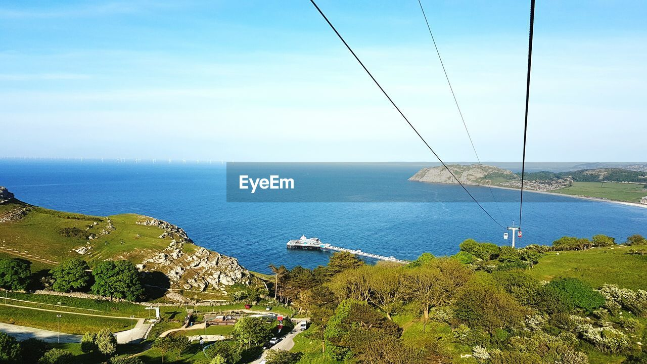 Overhead Cable Cars Over Coastline Against Sky