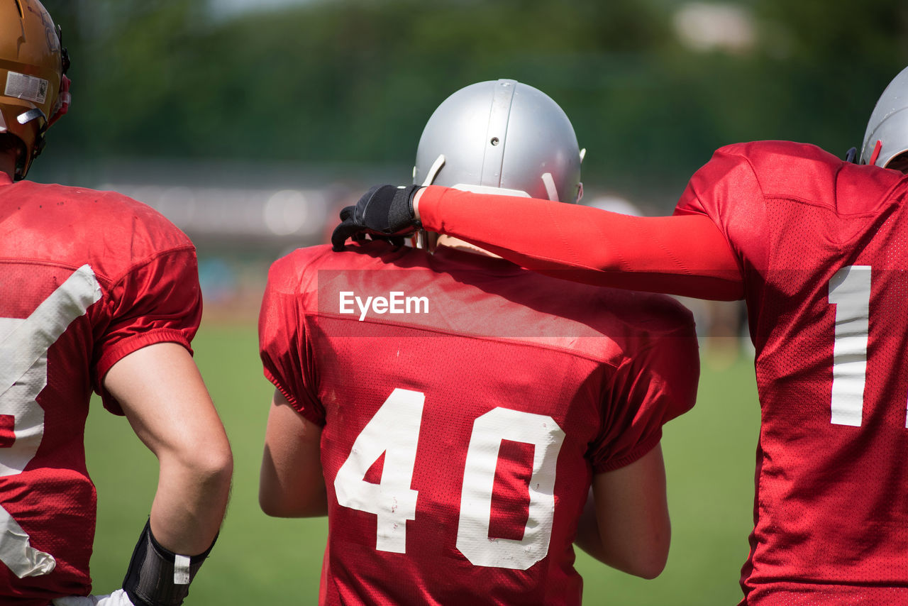 Rear View Of American Football Players On Field