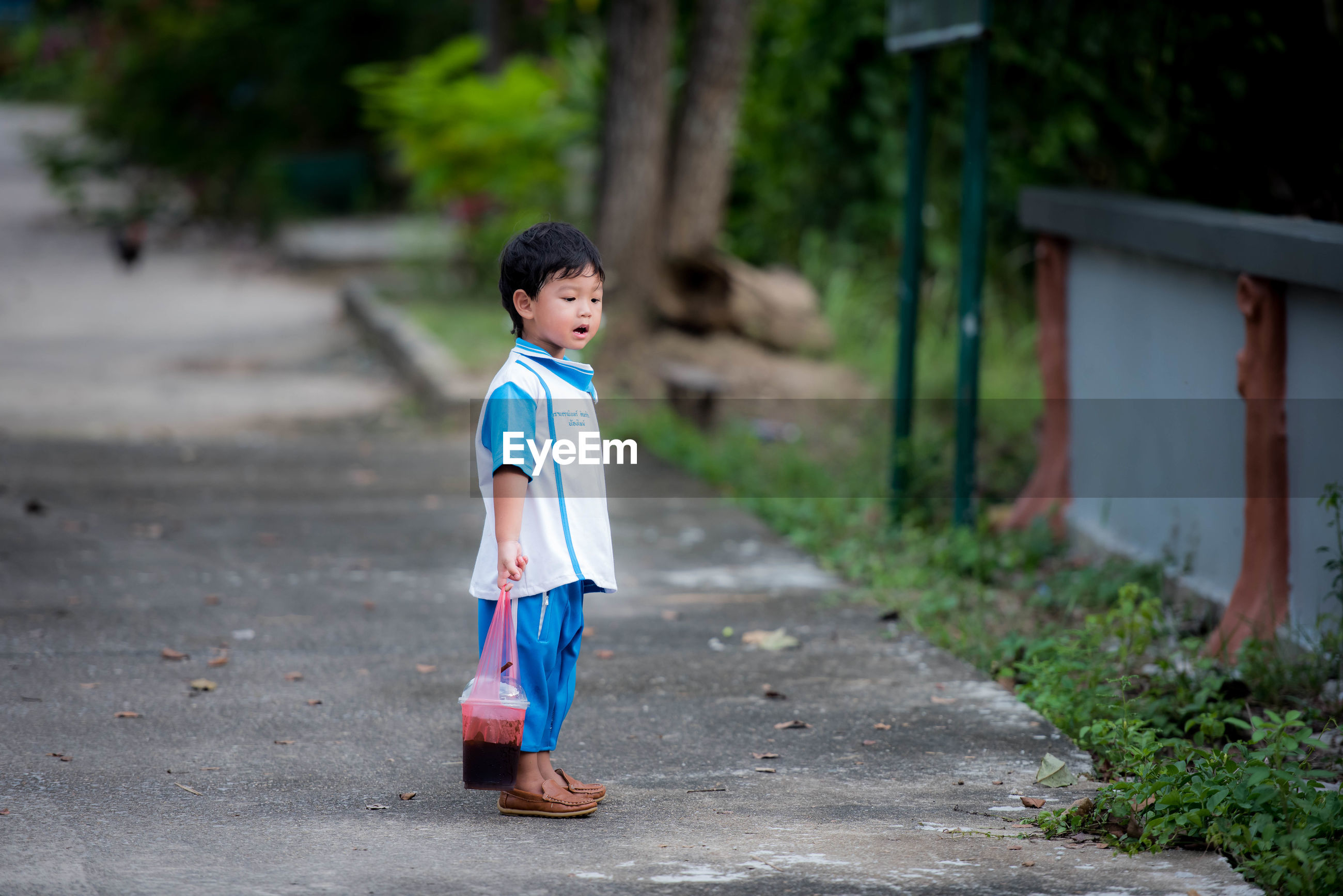 Side view of cute boy standing outdoors