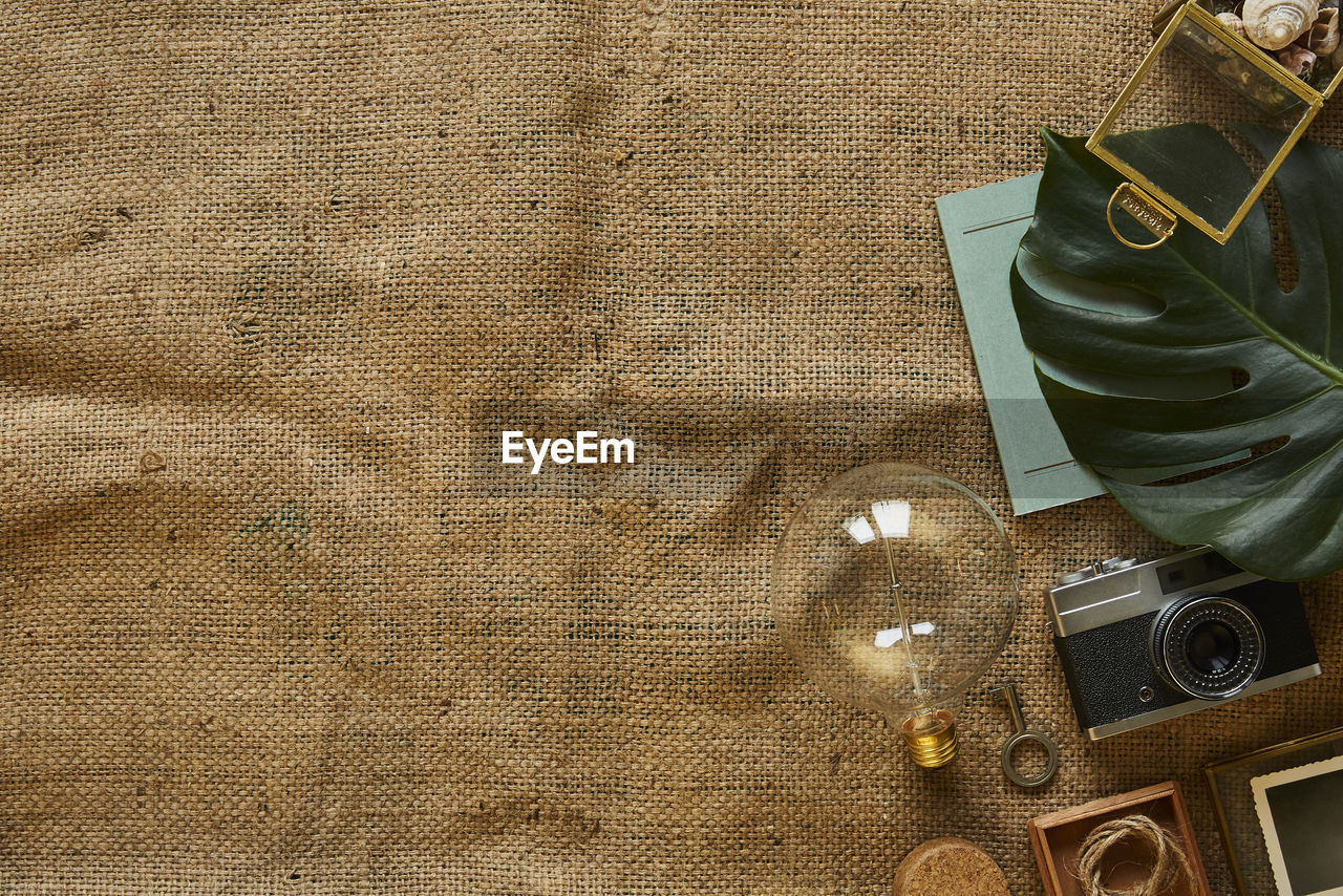 no people, still life, high angle view, indoors, textile, table, shoe, technology, close-up, brown, bag, retro styled, directly above, fashion, jute, thread, wood - material, collection, leather