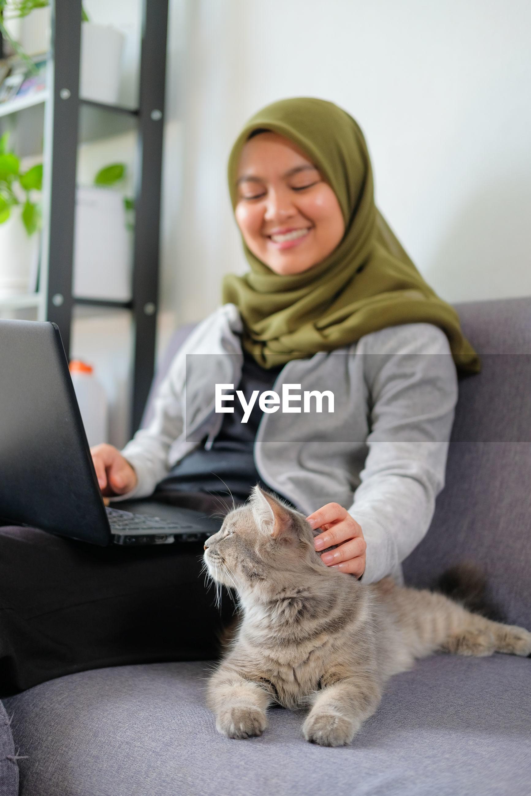 Smiling woman wearing hijab petting car while using laptop on sofa