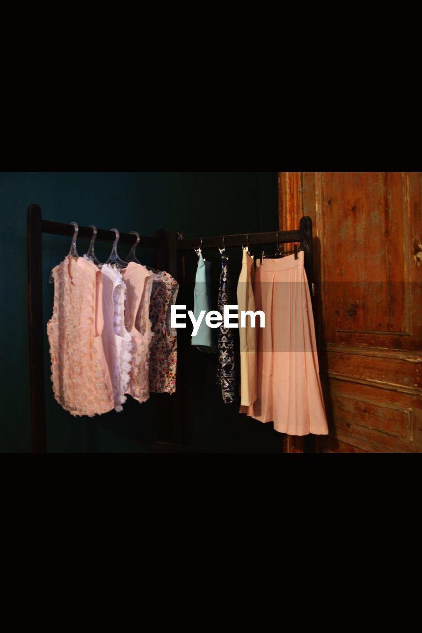 hanging, clothing, no people, coathanger, indoors, variation, black background, day