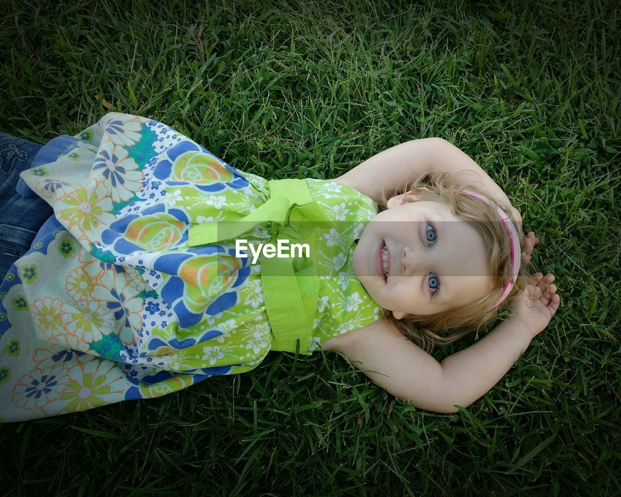 grass, childhood, looking at camera, portrait, high angle view, innocence, real people, field, lying down, girls, lying on back, one person, smiling, happiness, cute, day, leisure activity, green color, relaxation, growth, outdoors, nature