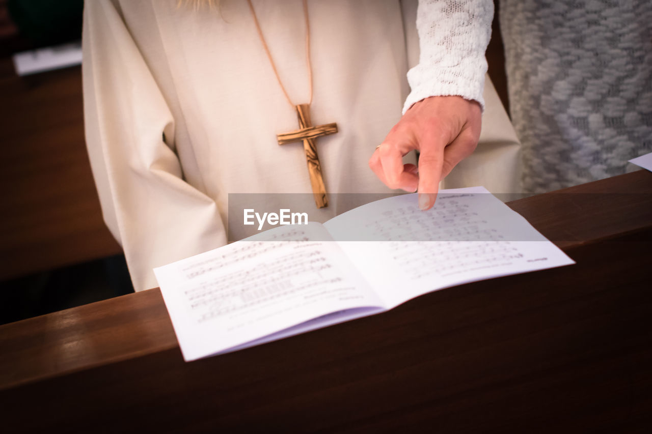 Midsection Of Mother Pointing Music Sheet By Daughter In Church During First Communion
