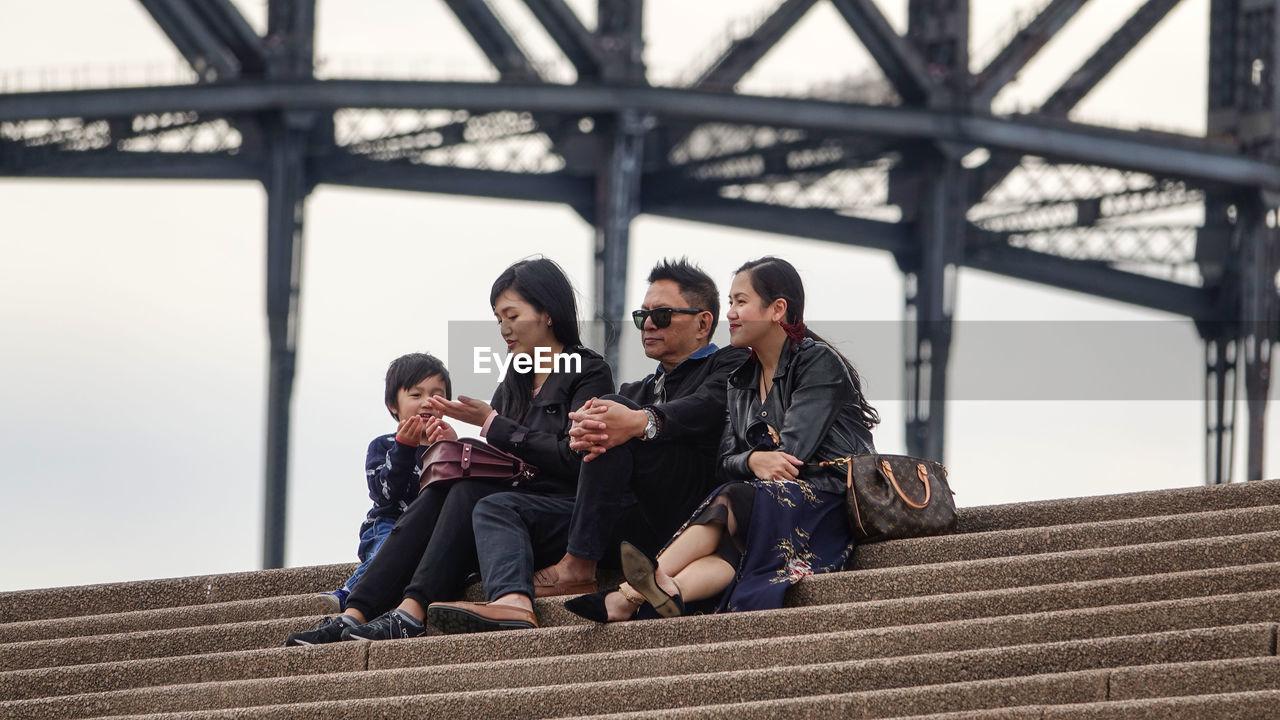 FULL LENGTH OF YOUNG COUPLE SITTING ON BRIDGE