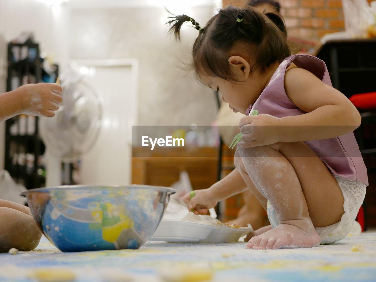 Baby preparing food while sitting on floor