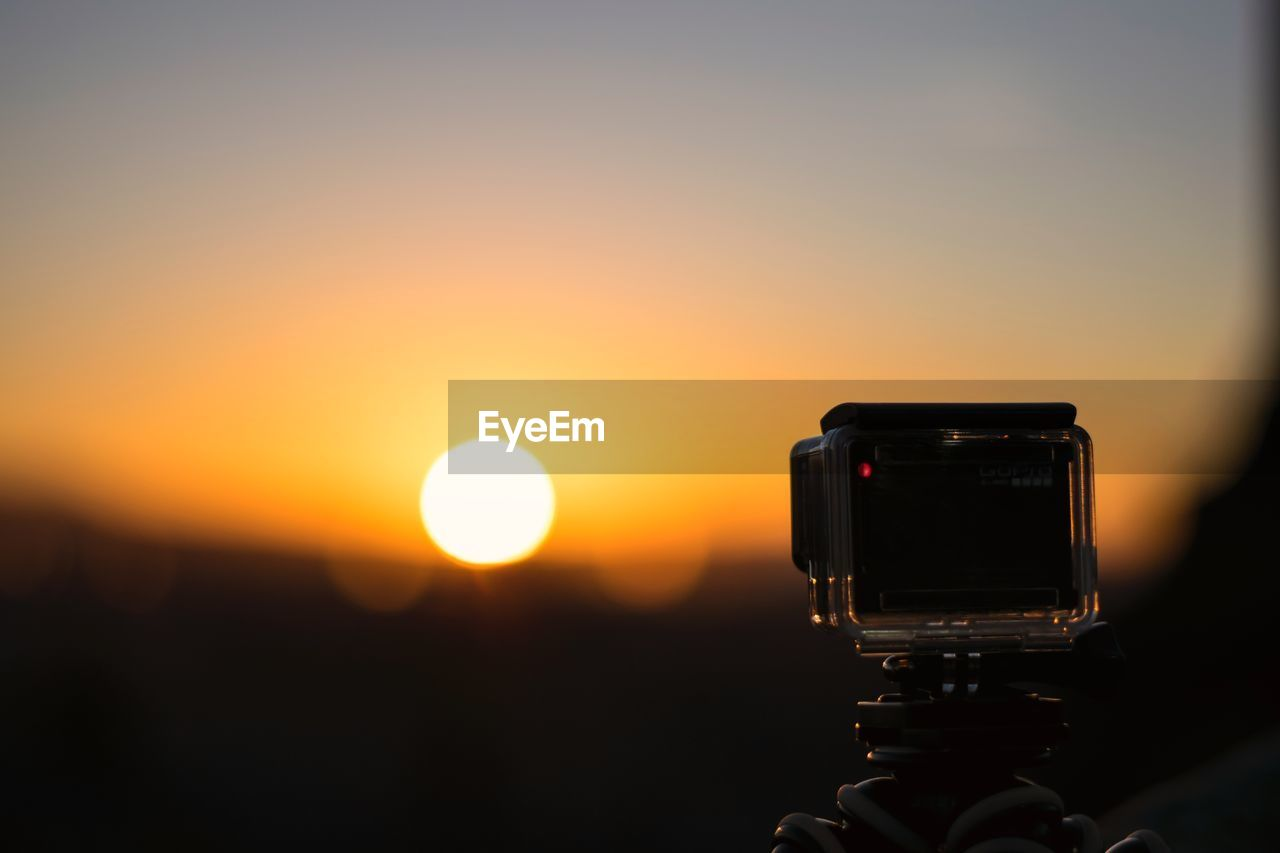 sunset, photography themes, technology, camera - photographic equipment, sky, photographic equipment, photographing, sun, orange color, holding, camera, digital camera, beauty in nature, silhouette, tripod, activity, human body part, close-up, one person, scenics - nature, modern, outdoors, photographer, filming