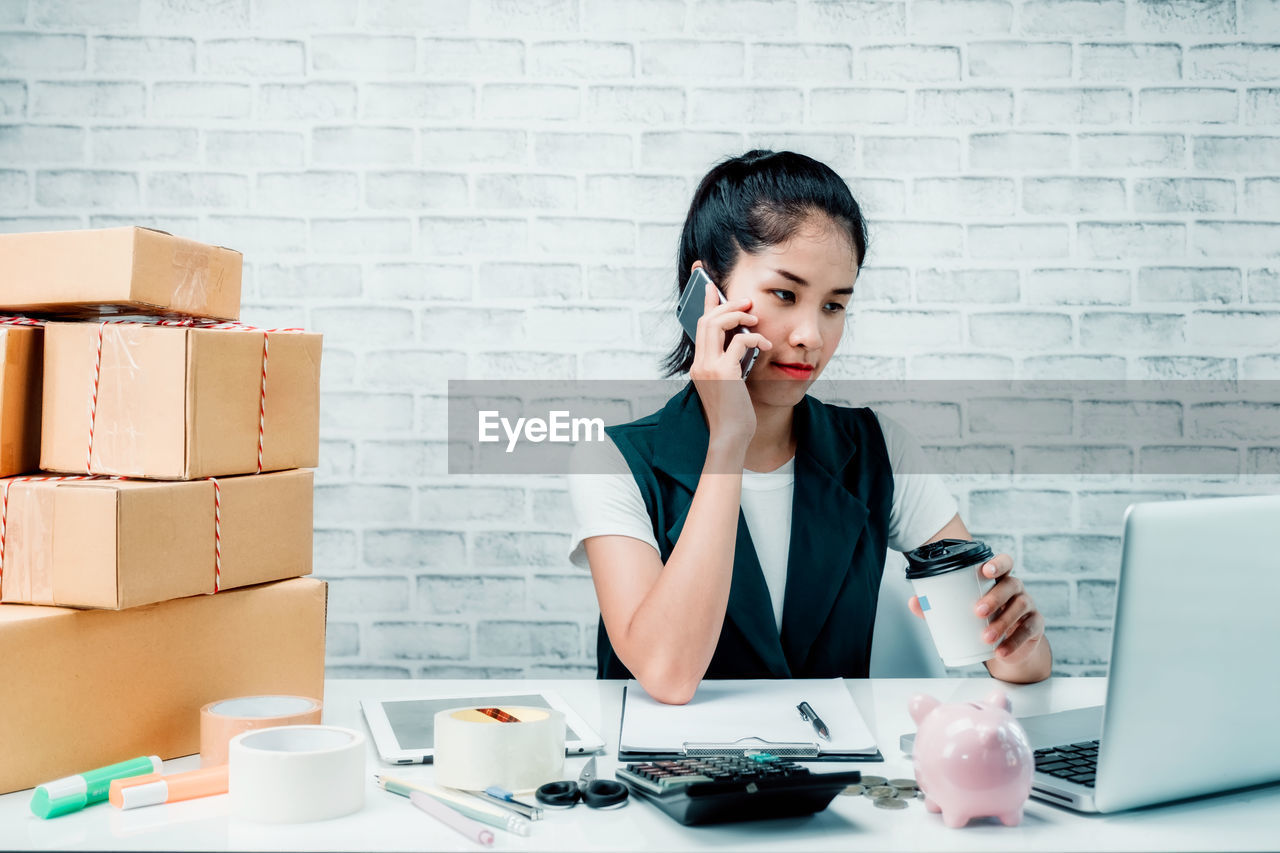 wireless technology, communication, technology, business, front view, business person, one person, table, indoors, portable information device, connection, adult, computer, women, young adult, mobile phone, telephone, using phone, office, holding, brick, entrepreneur, new business