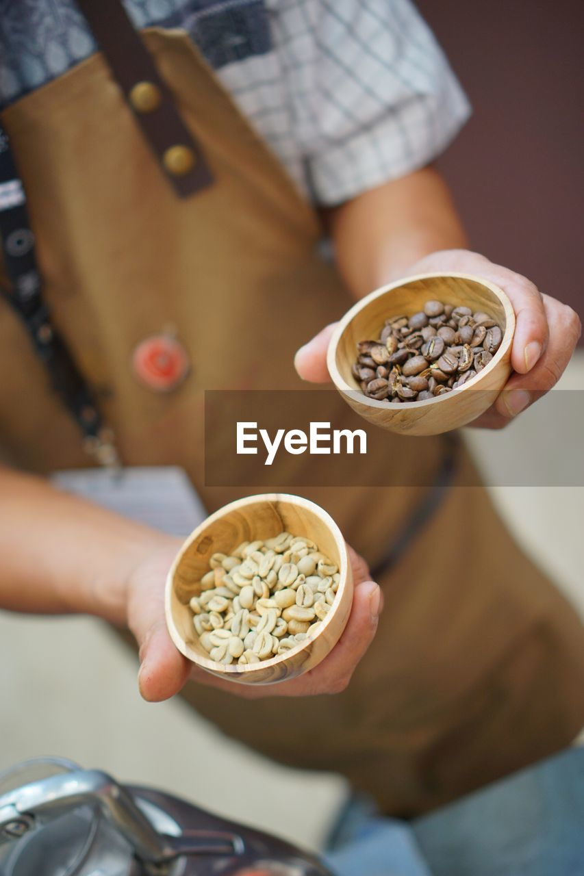 Midsection of man holding coffee beans in bowls