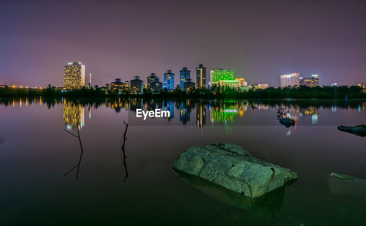 water, reflection, sky, architecture, built structure, building exterior, nature, lake, waterfront, night, illuminated, building, city, no people, solid, tranquility, outdoors, rock, dusk, office building exterior, skyscraper