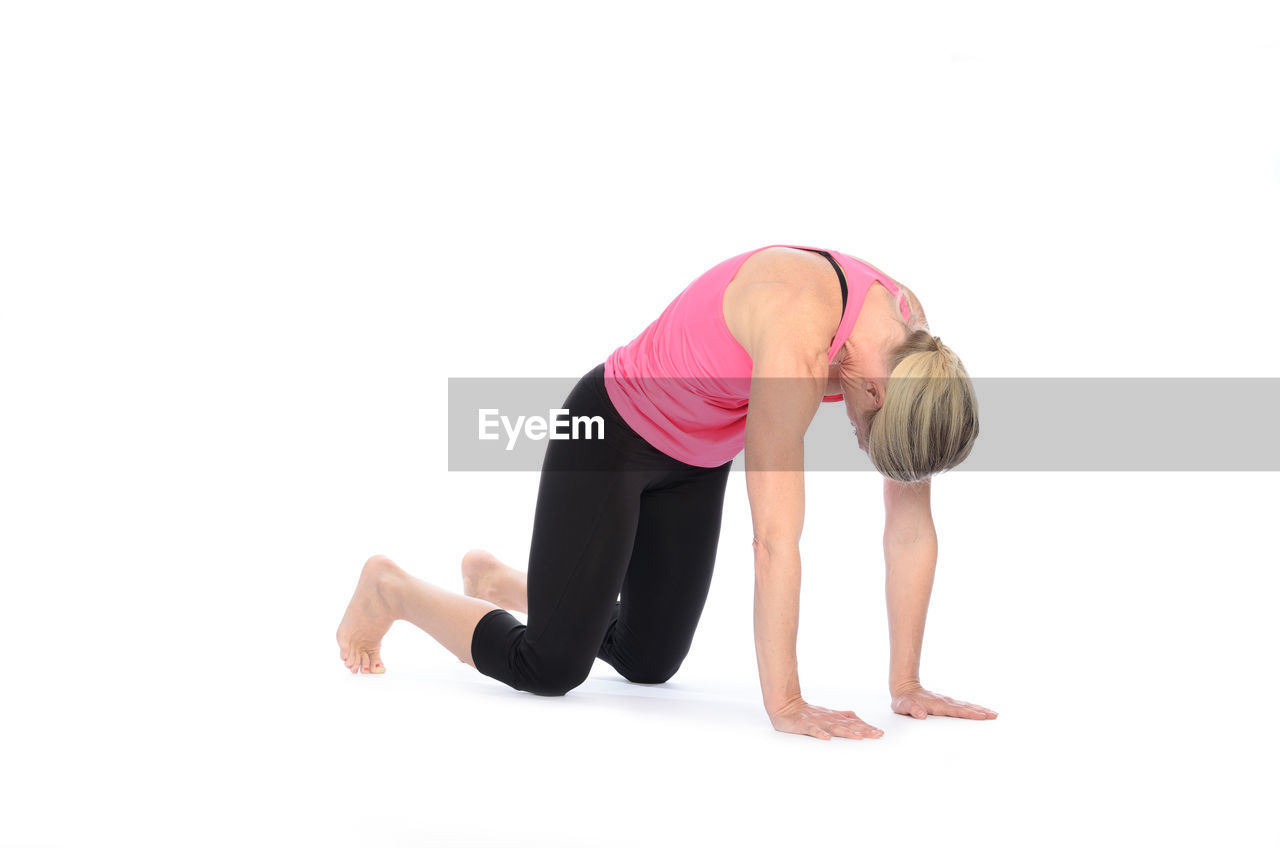 Woman Practicing Cat Pose Against White Background