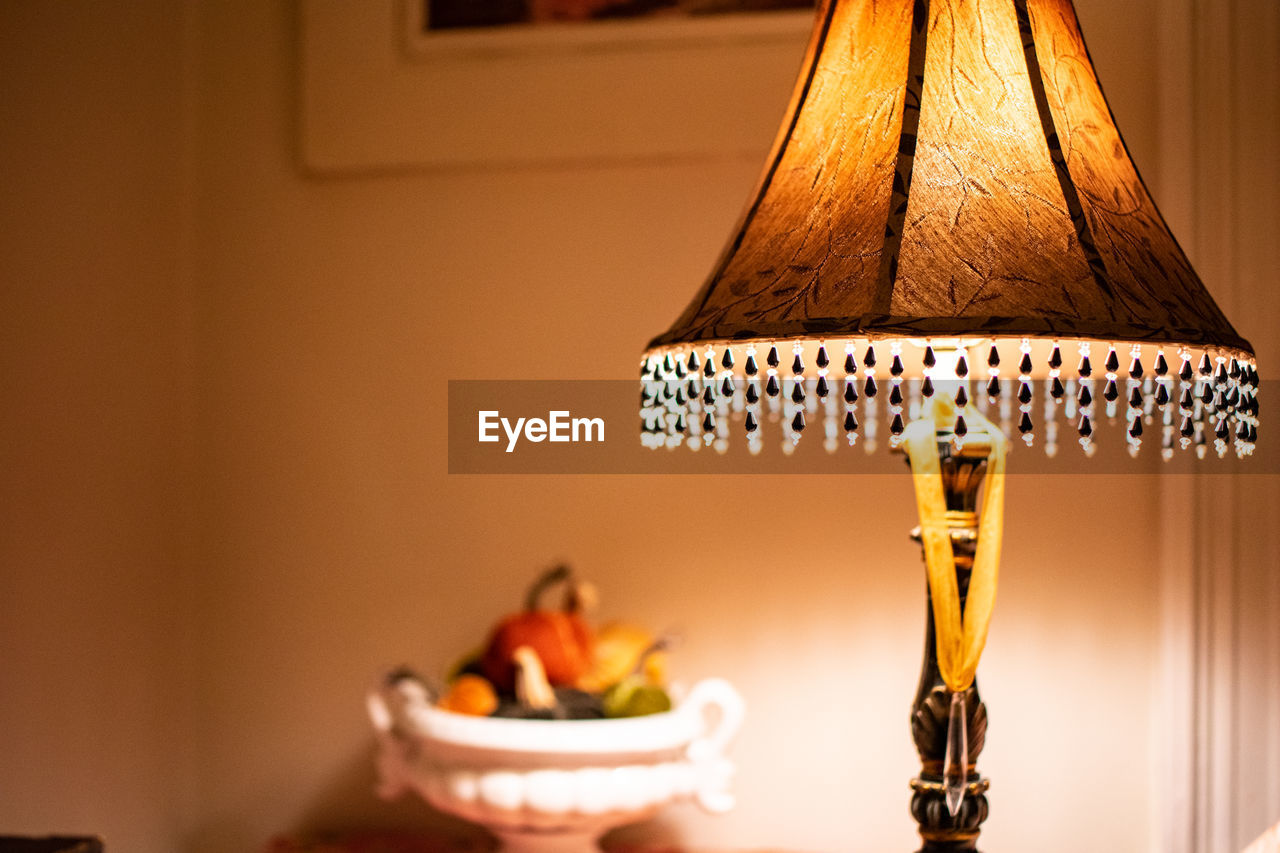 lighting equipment, focus on foreground, indoors, no people, electric lamp, illuminated, close-up, home interior, table, lamp shade, electricity, electric light, candle, wall - building feature, light, still life, art and craft, metal, selective focus, decoration