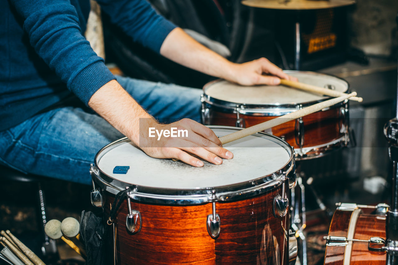 Midsection of man playing drums at music concert