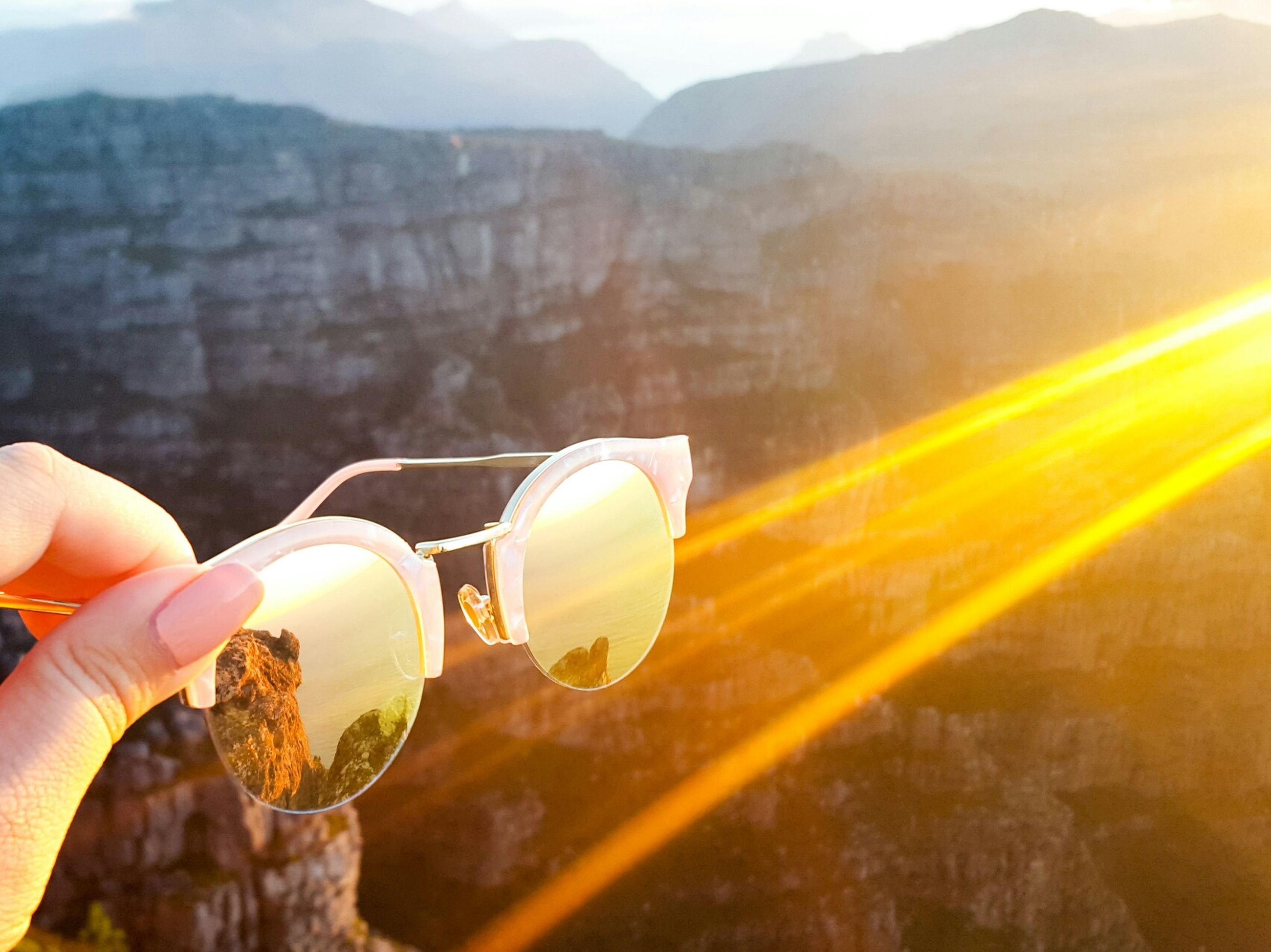 Cropped hand of woman holding sunglasses against table mountain