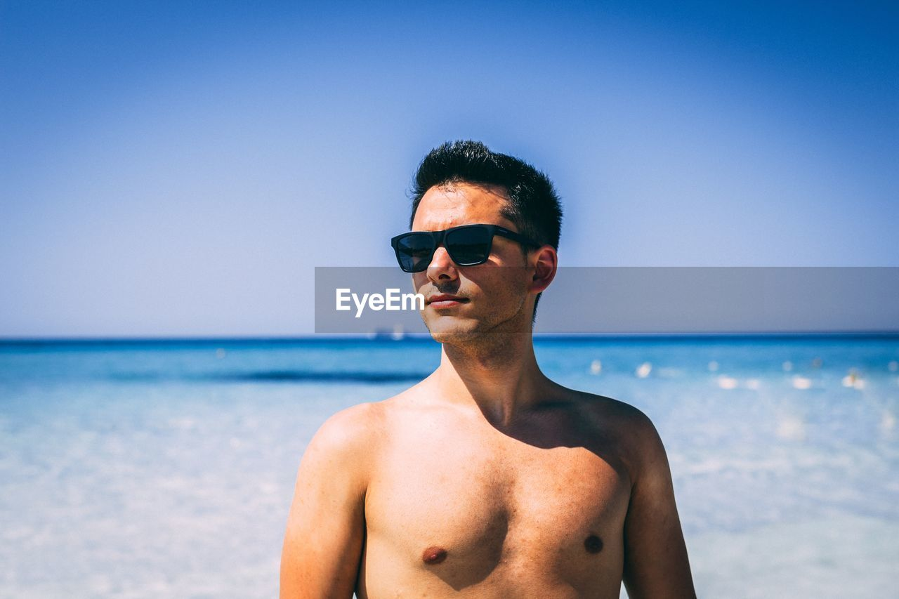 Shirtless young man looking away standing at beach against sky