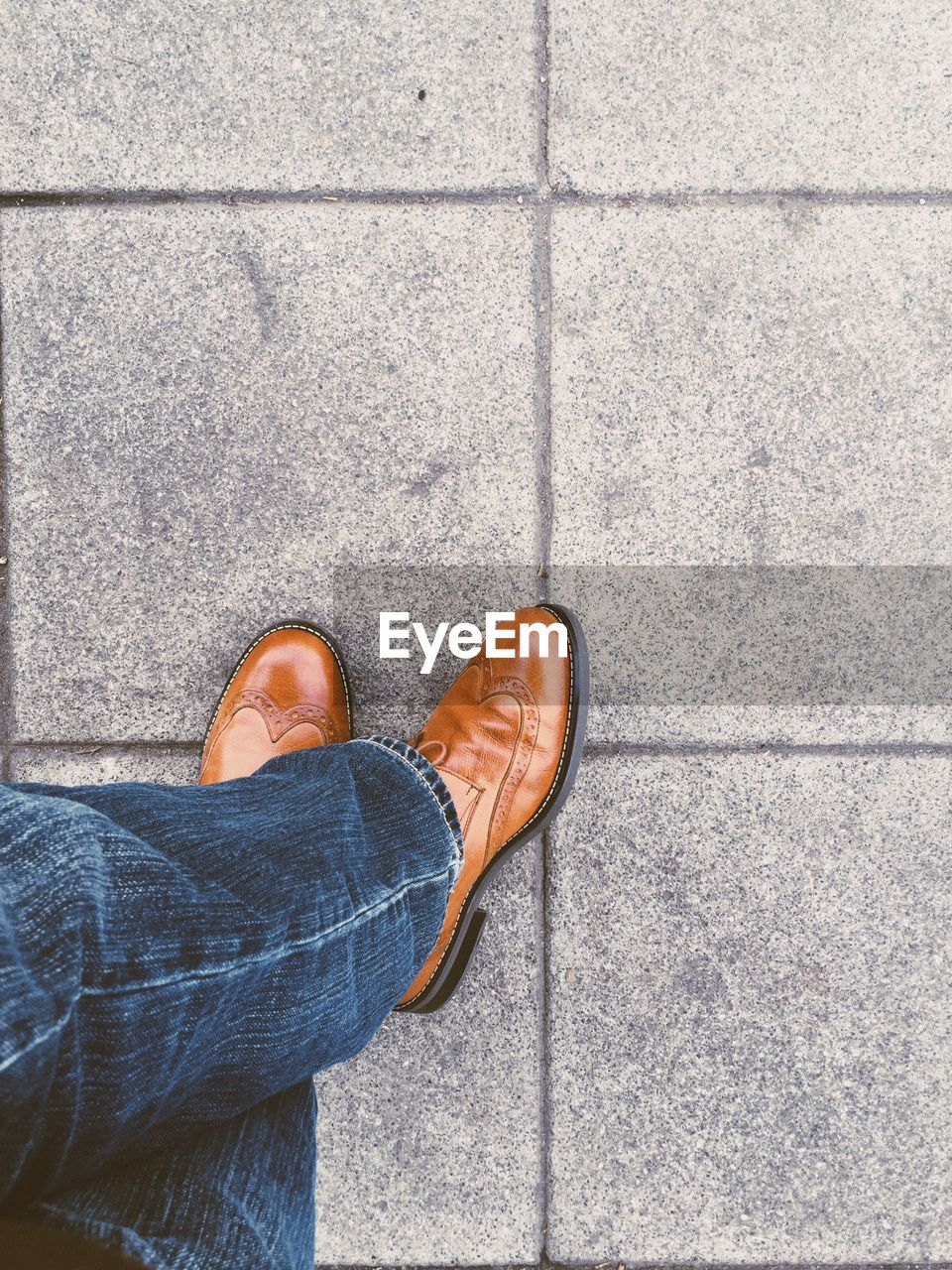 Low section of man in shoes standing on footpath