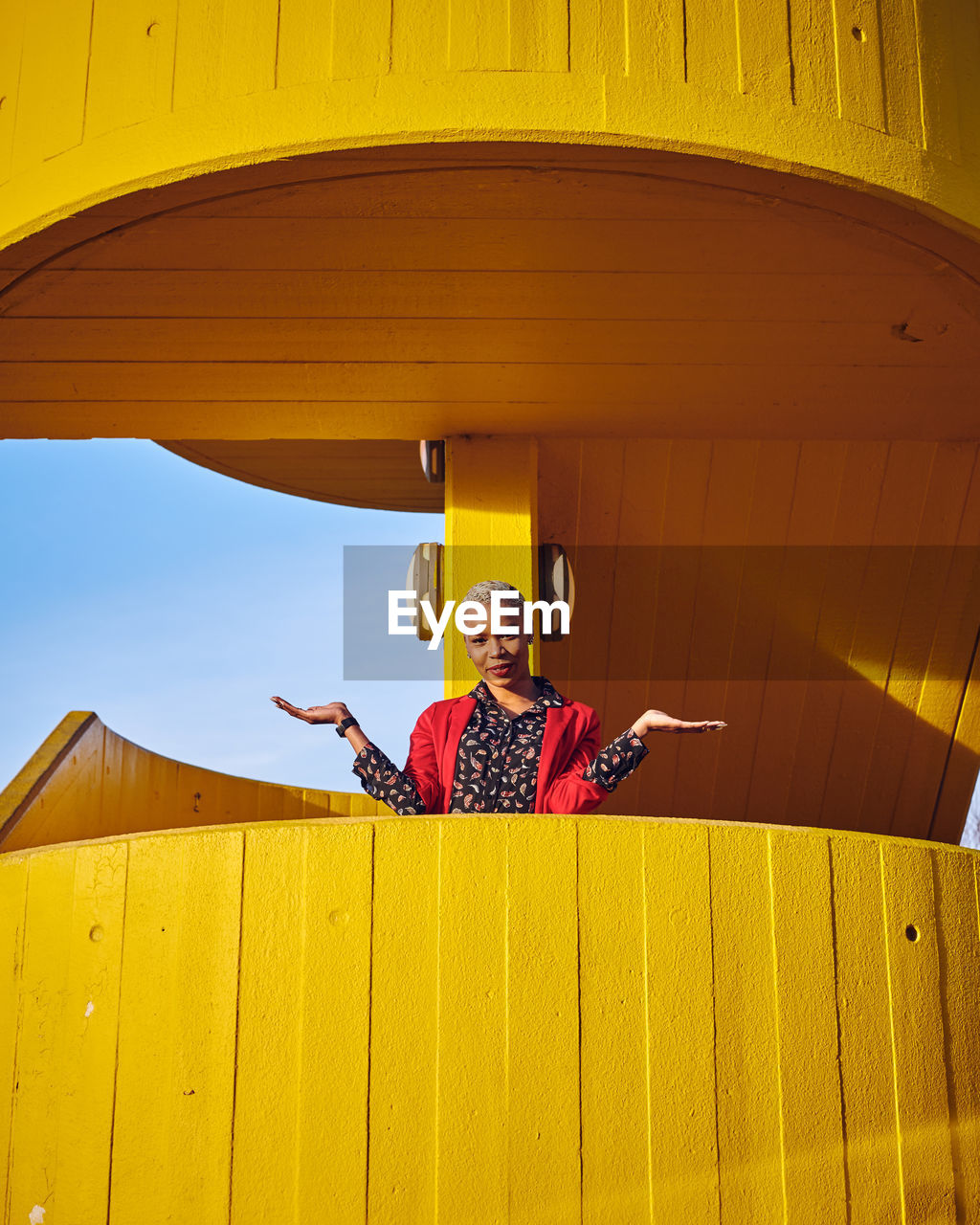 Low Angle Portrait Of Woman Standing At Yellow Balcony
