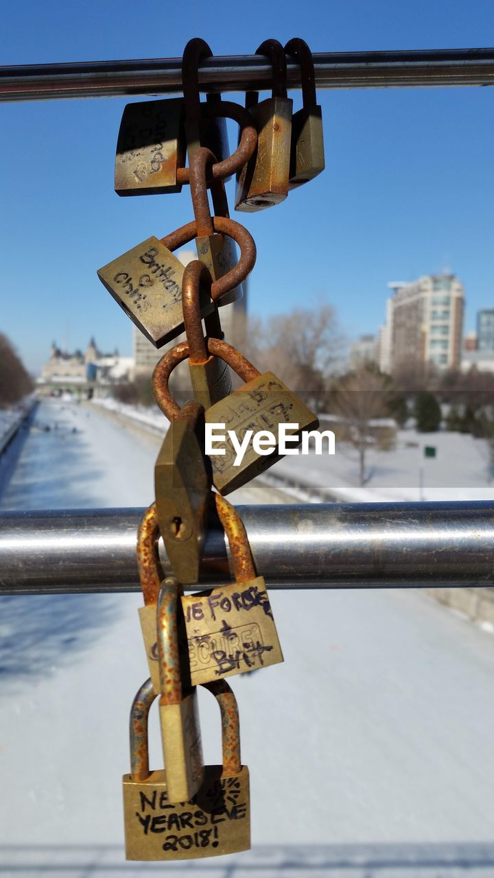 metal, padlock, safety, hanging, love lock, focus on foreground, lock, close-up, security, day, text, no people, railing, protection, architecture, sky, connection, communication, hope - concept, love, outdoors, positive emotion, bridge - man made structure