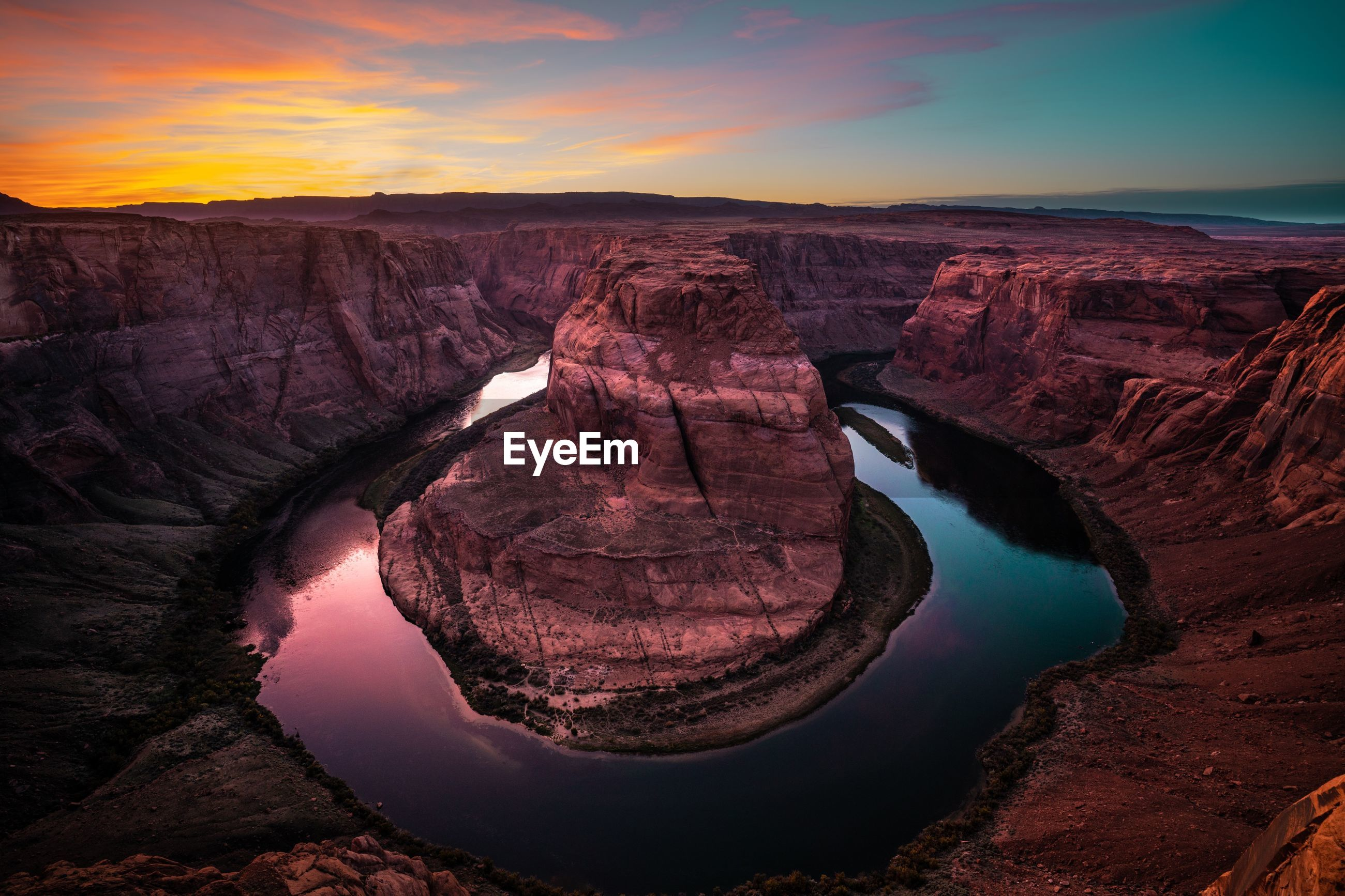 Scenic view of horseshoe bend against sky during sunset