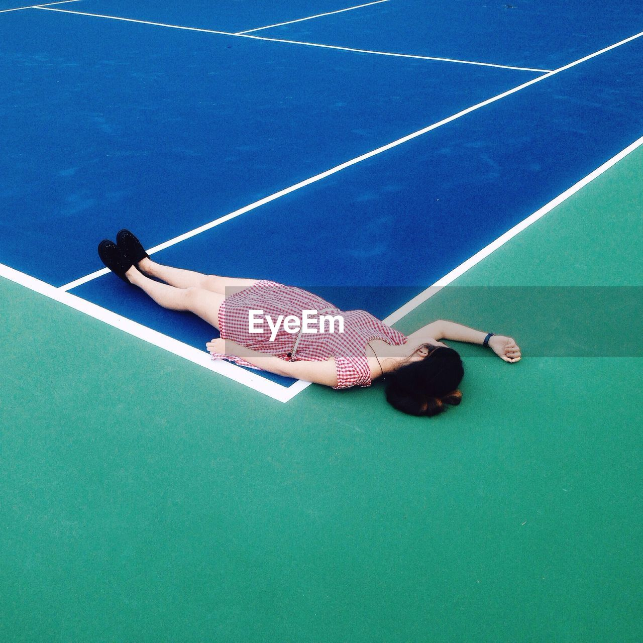 High Angle View Of Woman Sleeping At Tennis Field