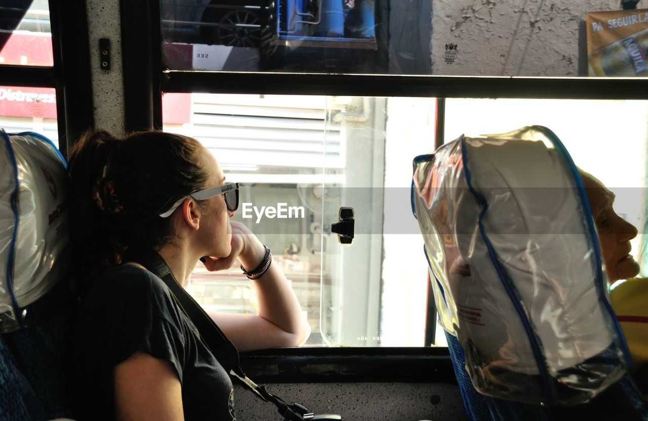 Woman looking though window while sitting in bus