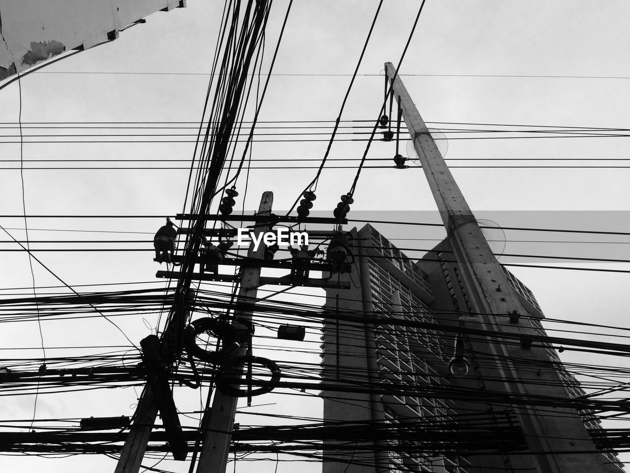 Low Angle View Of Electricity Pylons By Building Against Sky