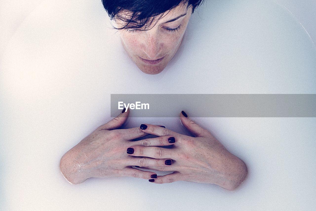 High Angle View Of Woman Lying In Bath Tub