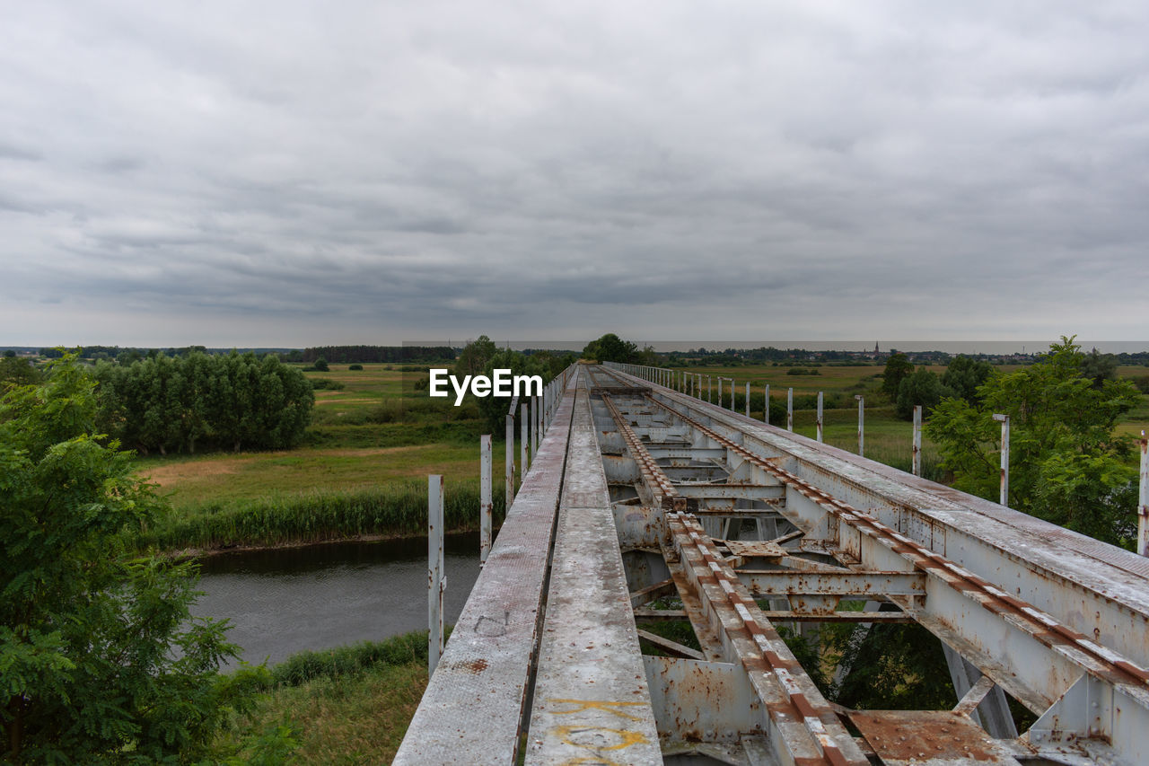 VIEW OF BRIDGE OVER FIELD AGAINST SKY