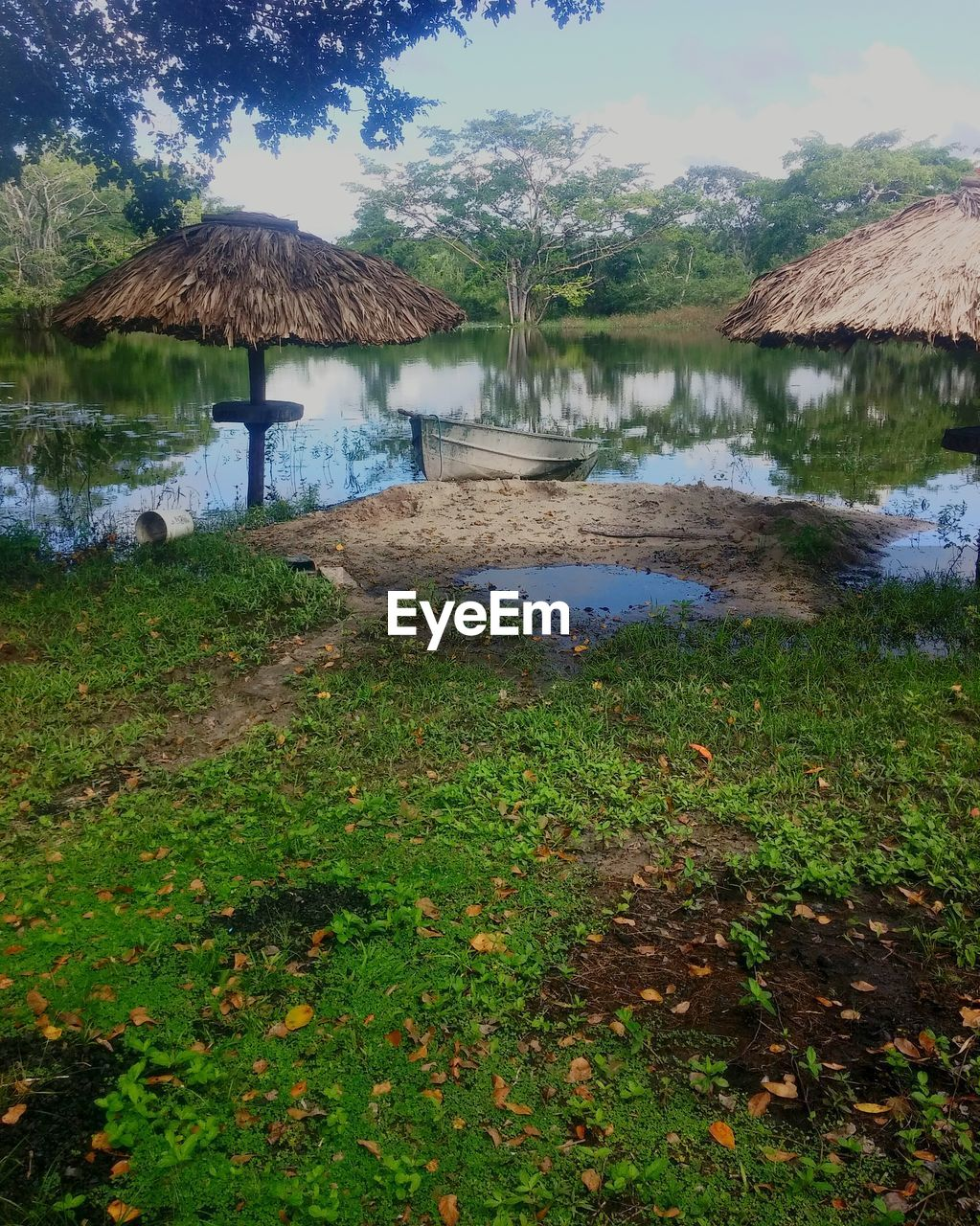 water, nature, thatched roof, outdoors, grass, beauty in nature, lake, tranquility, no people, scenics, day, tree, sky
