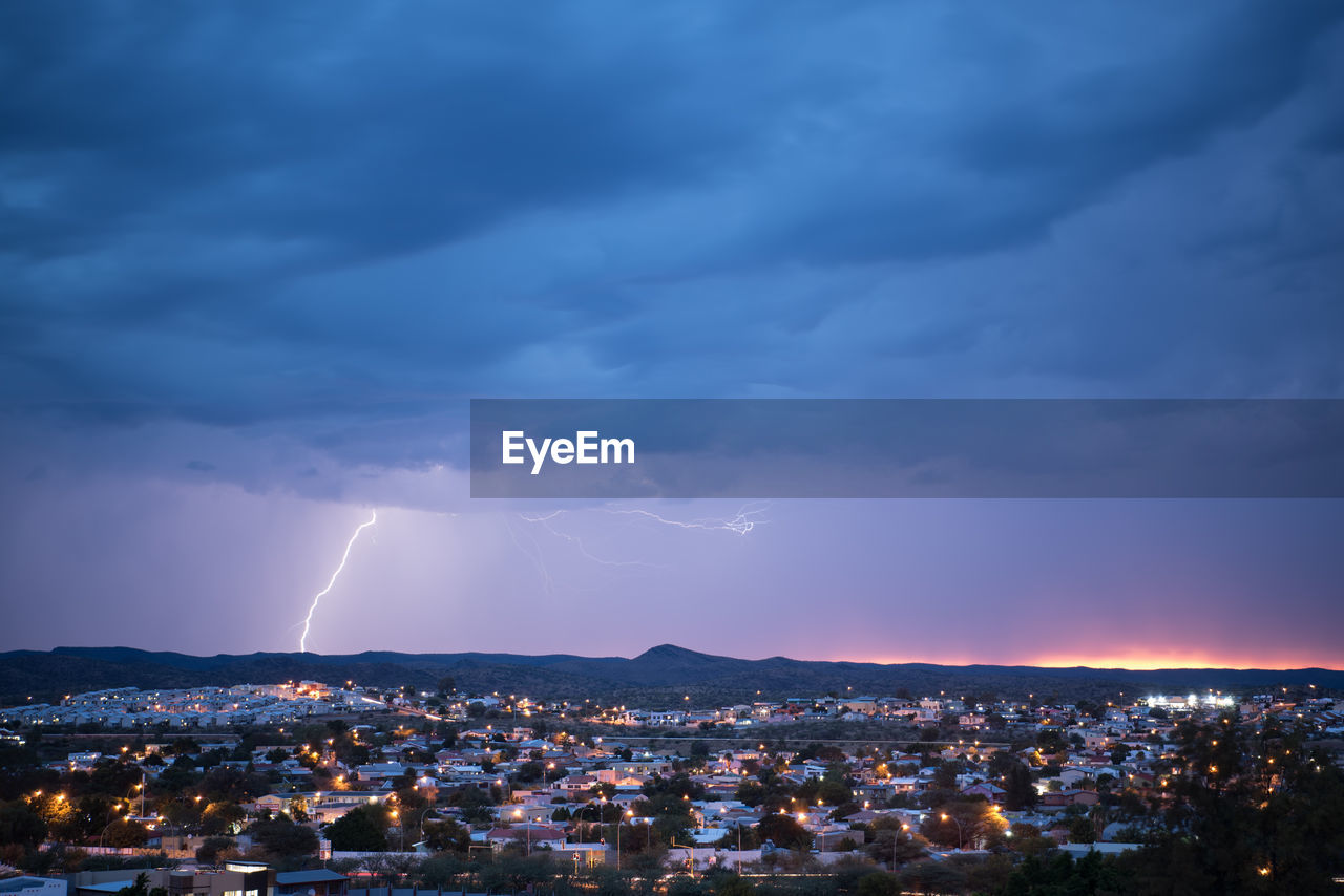 Aerial View Of Illuminated Cityscape Against Cloudy Sky During Storm