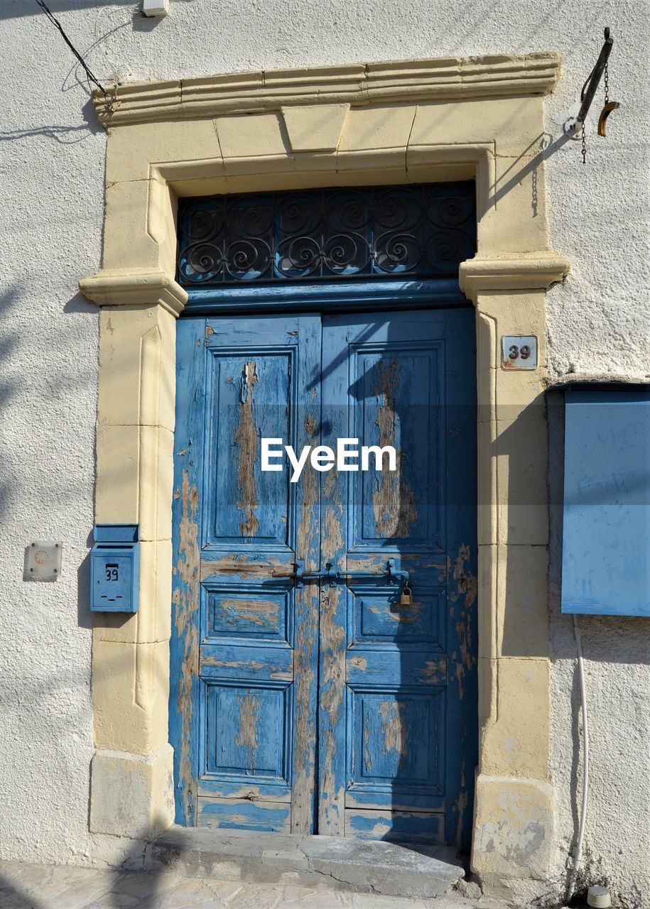 architecture, built structure, entrance, building exterior, door, closed, building, blue, day, house, security, protection, no people, wall - building feature, safety, wood - material, outdoors, sunlight, residential district, old