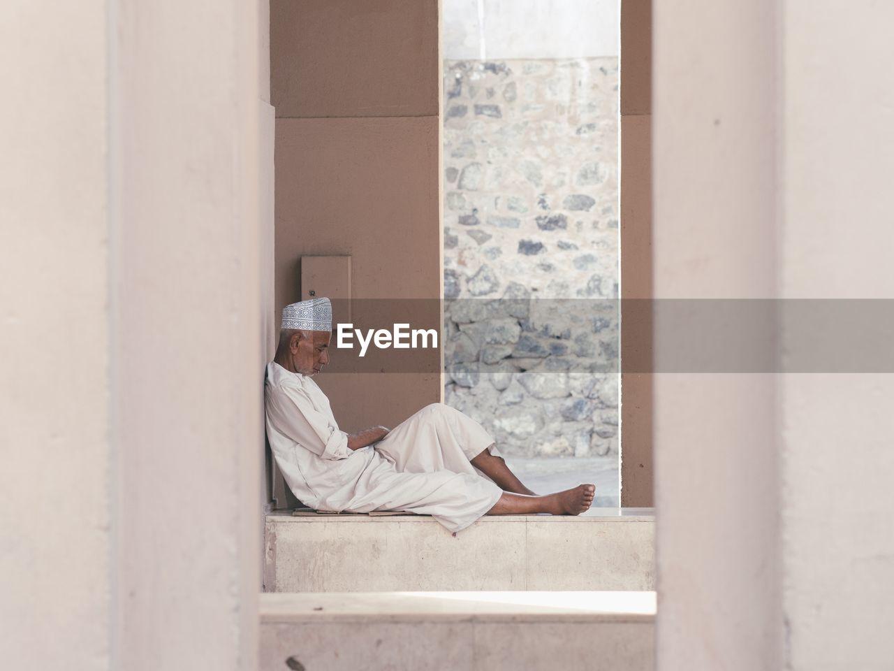 MAN SLEEPING ON WALL