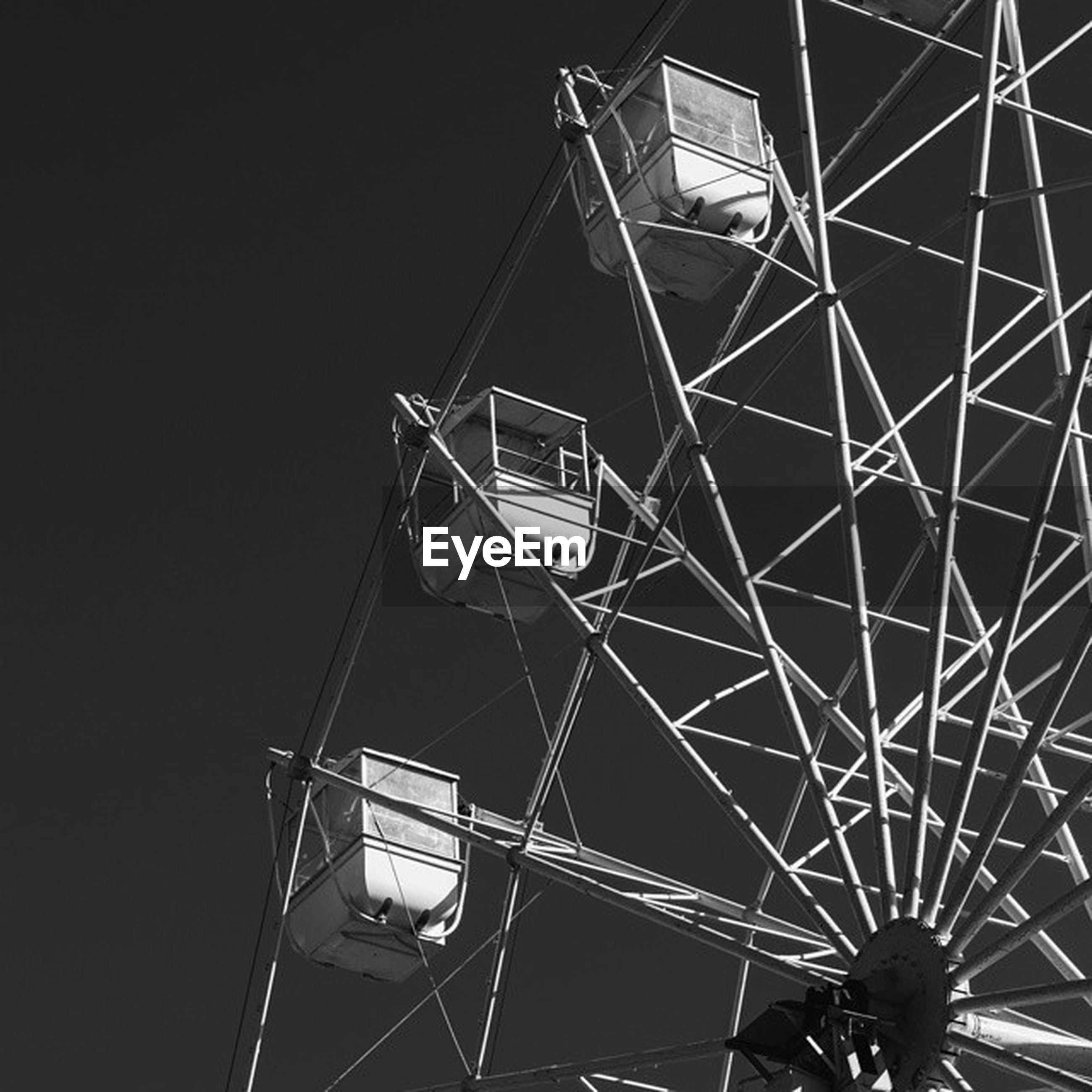 low angle view, metal, amusement park ride, ferris wheel, amusement park, arts culture and entertainment, metallic, built structure, pattern, architecture, geometric shape, no people, clear sky, directly below, day, sky, outdoors, fuel and power generation