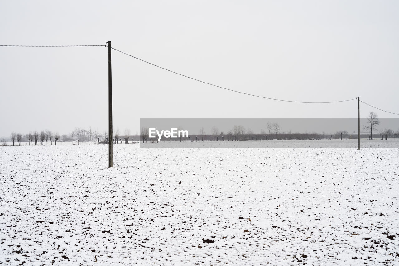 winter, cold temperature, sky, snow, tranquility, nature, land, tranquil scene, scenics - nature, beauty in nature, day, cable, covering, environment, no people, field, landscape, clear sky, non-urban scene, outdoors, electricity, climate
