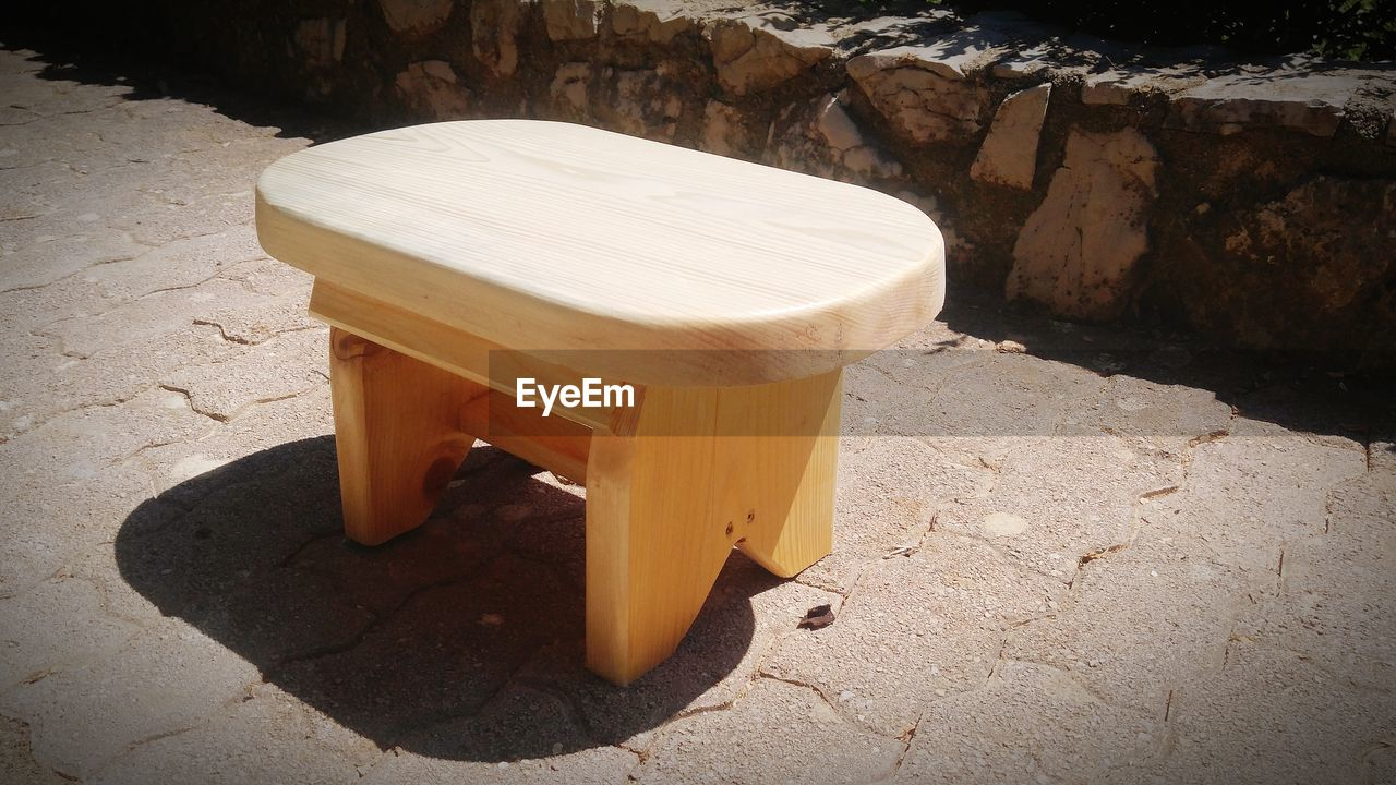 High angle view of wooden stool on street during sunny day